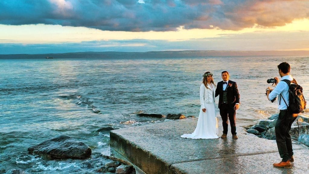 A bride and groom on the beach having their photo taken, waves crash in the background.